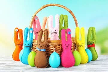 Composition with funny handmade Easter rabbits in wicker basket