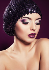 portrait of beautiful model in hat with purple make up