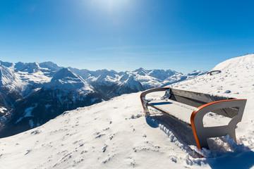 Bench in ski resort Bad Gastein in snowy mountains, Austria