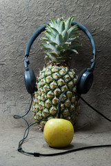 Pineapple with headphones and apple.