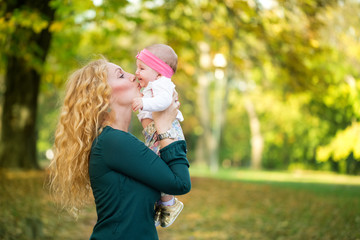 Mother and baby kissing in nature outdoor