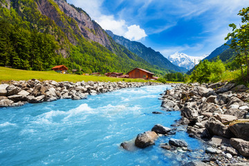 Foto op Canvas Blauw Swiss landscape with river stream and houses