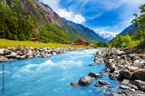 Wall mural Swiss landscape with river stream and houses