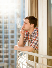 young man smoking cigarette out of window