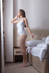 Image of cute slim girl posing in hotel bedroom