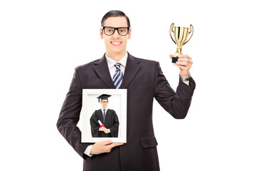 Man holding trophy and picture of his graduation