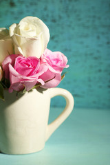 Beautiful roses in cup on green background