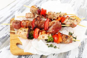 Fototapete - Pork kebab on wooden table close up