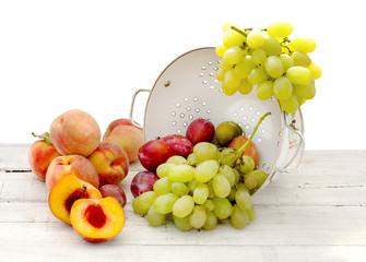 fresh summer fruits inside ceramic colander