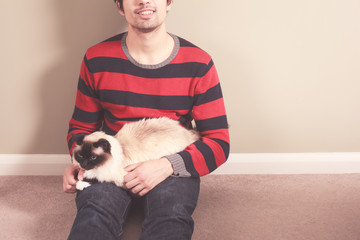 Young man and cat sitting on the floor