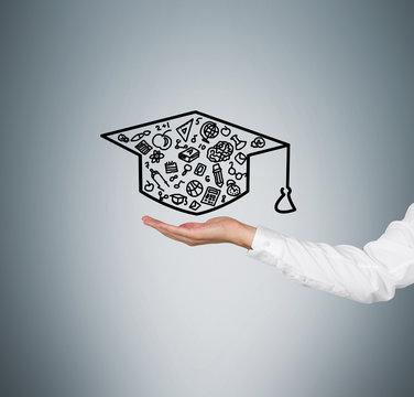 A hand holding a graduation hat
