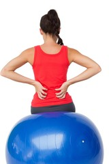 Rear view of a fit young woman sitting on exercise ball