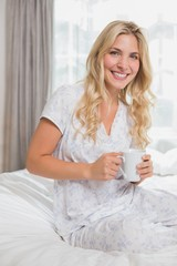 Beautiful casual woman holding coffee cup in bed