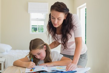 Woman assisting daughter in drawing