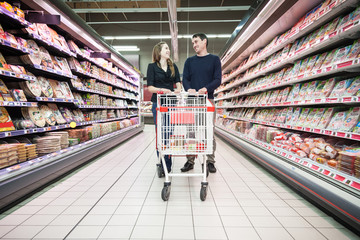 25 years old couple smiling in a supermarket and pulling a cart