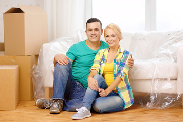smiling couple sitting on the floor in new house