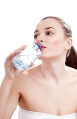 Young woman drinking mineral water bottle, isolated on white