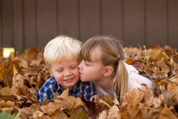 Little girl kissing a little boy laying in leaf pile leaves