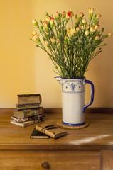 carnation flowers bouquet in vase with books on table