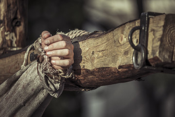 Nailed hand on wooden cross. Jesus Christ crucifixion