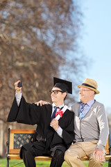 Student and his proud father taking selfie in park
