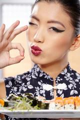 Beautiful sushi woman showing a plate of sushi.
