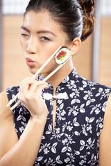 beautiful asian woman eating sushi with chopsticks