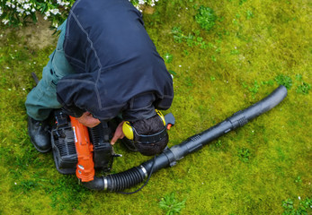 gardener using a gas blower in a park
