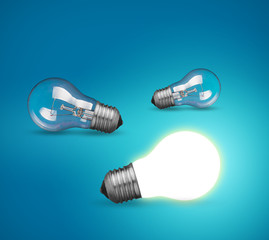 idea concept with glowing light bulb on blue background