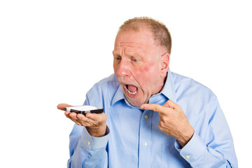 Angry senior man screaming on cell phone, white background