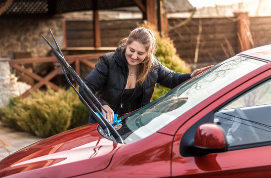 beautiful woman washing car windscreen
