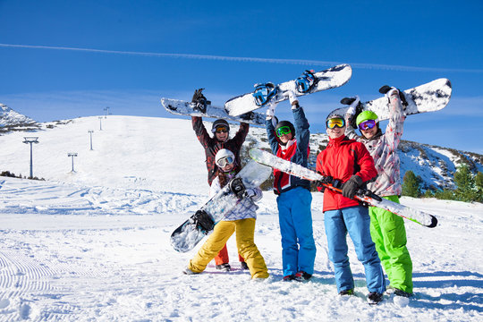 Five snowboarders holding oards and skies together