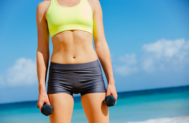 Close-up of torso of fitness woman holding barbells