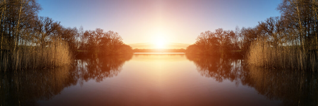 Stunning Spring sunrise landscape over lake with reflections and