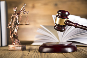 Lady of justice, wooden & gold gavel and books on wooden table