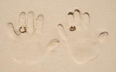 Hand print on sand beach with wedding rings.