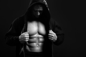black and white strong man in the hood showing his abs