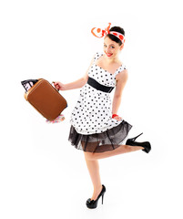 Pinup girl with suitcase in dress spotted, full length portrait