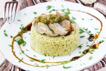 Couscous with pesto sauce, fried sliced pork, tasty dish
