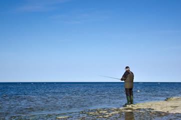 Man fishing at a flat rock coast