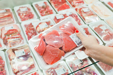 Keuken foto achterwand Vlees Packaged meat with woman hand in the supermarket