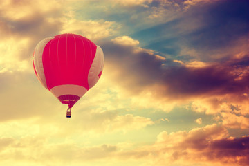 Hot Air Balloon Flying over Dramatic Sunset Sky