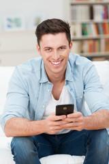 junger mann zu hause mit smartphone