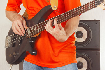 Rock musician playing the electric bass guitar closeup
