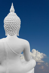 Some behind the White Buddha with blue clouds in the background