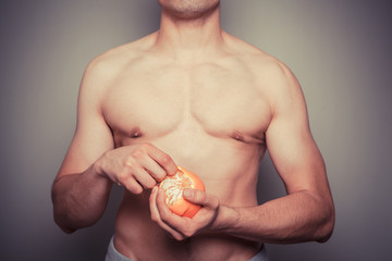Athletic shirtless man peeling an orange