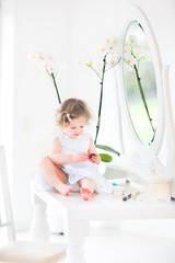 Pretty toddler girl with curly hair wearing a white dress
