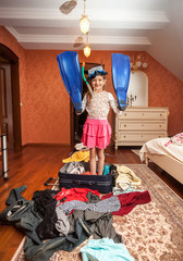 girl in mask,snorkel and flippers standing in suitcase