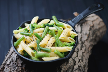 Frying pan with penne pasta and vegetables on wooden logs