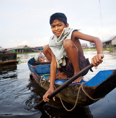 Boy Traveling by Boat in Floating Village